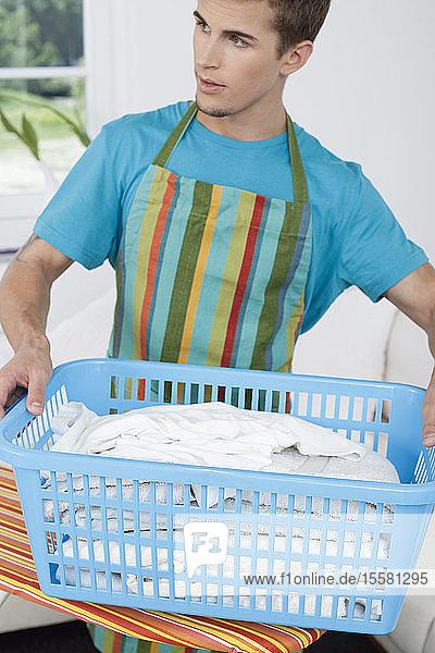 Deutschland  Augsburg  Mann hält Kleiderkorb