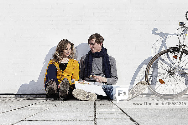 Germany  Bavaria  Munich  Young couple having pizza  smiling