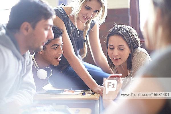 Schüler zeigt Handy vor Klassenkameraden im Klassenzimmer