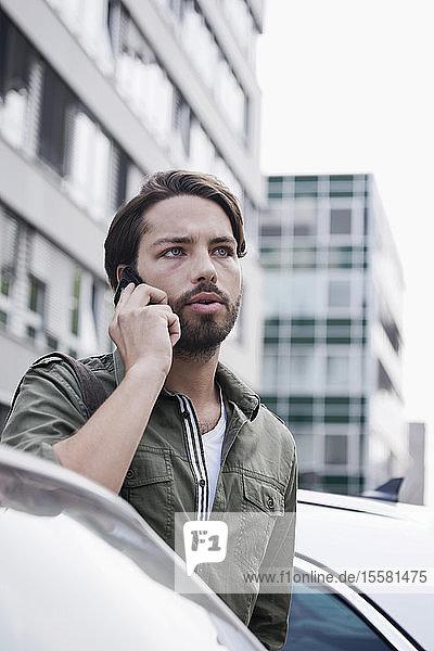 Deutschland  Köln  Junger Mann am Telefon in der Nähe des Autos