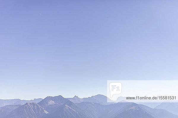 Blick auf das Karwendelgebirge vor klarem  blauem Himmel bei nebligem Wetter  Bayern  Deutschland