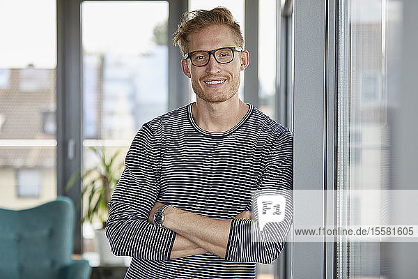 Portrait of smiling young man leaning against window