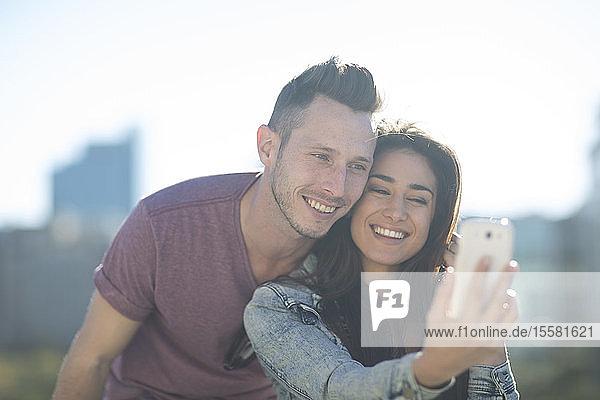 Porträt eines glücklichen jungen Paares  das sich mit einem Smartphone ein Selfie gönnt