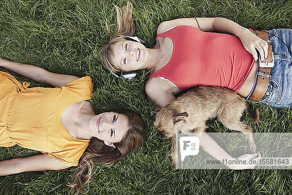 Deutschland  Köln  Junge Frau im Gras liegend mit Hund  lächelnd  Porträt