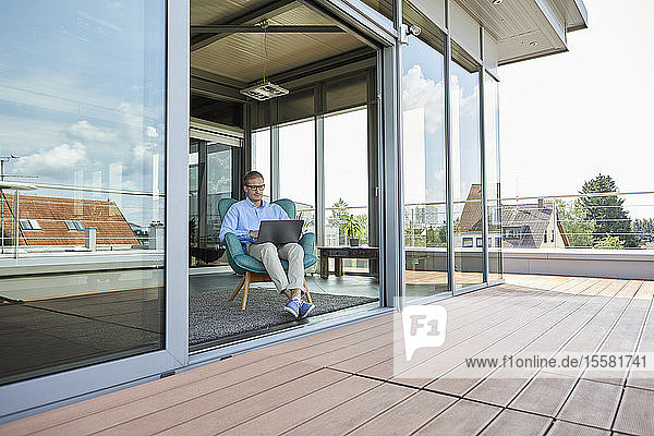 Young man sitting in armchair at balcony door using laptop