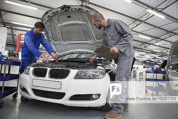 Zwei Automechaniker bei der Arbeit in der Reparaturwerkstatt