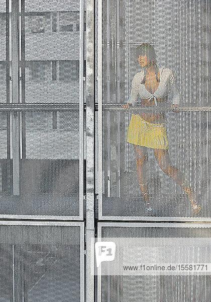Österreich  Junge Frau hinter Glasfenster stehend