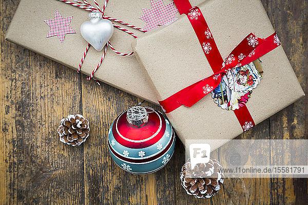 Eingepackte Weihnachtsgeschenke  Weihnachtskugeln und Tannenzapfen auf dunklem Holz