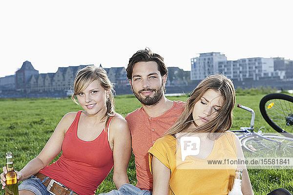 Deutschland  Köln  Junger Mann und Frau mit Bierflasche im Gras  lächelnd