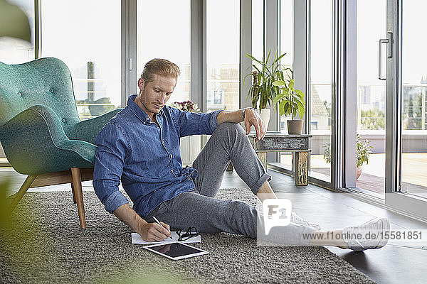 Young man sitting on carpet at home taking notes