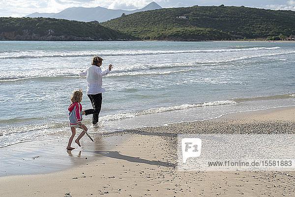 Griechenland  Parga  Mutter und Tochter laufen an der Strandpromenade