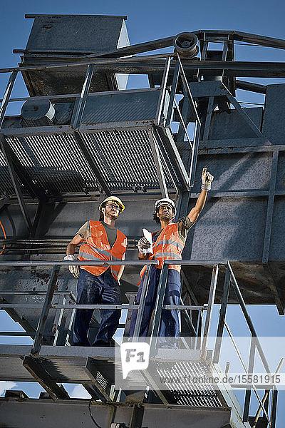 Deutschland  Augsburg  Zwei Arbeiter stehen auf großer Maschine