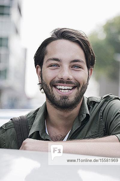 Deutschland  Köln  Junger Mann beim Auto  lächelnd  Porträt