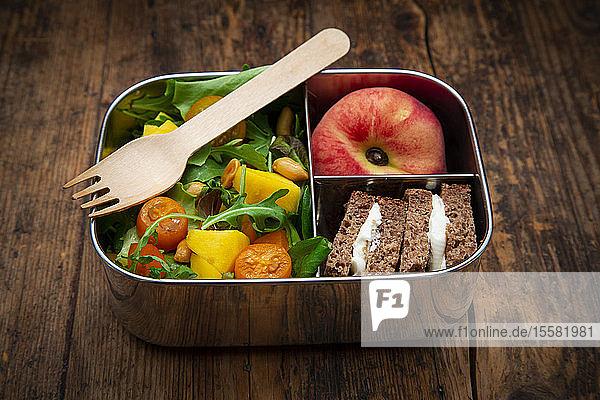 Nahaufnahme von gesundem Salat mit Sandwiches und Obst in Lunchbox auf dem Tisch