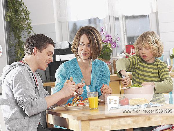 Deutschland  Augsburg  Mutter und Kinder essen Nudeln