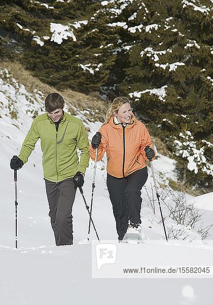 Deutschland  Bayern  Junges Paar Schneeschuhwandern