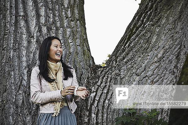 Deutschland  Köln  Junge Frau neben Baumstamm im Park  lächelnd