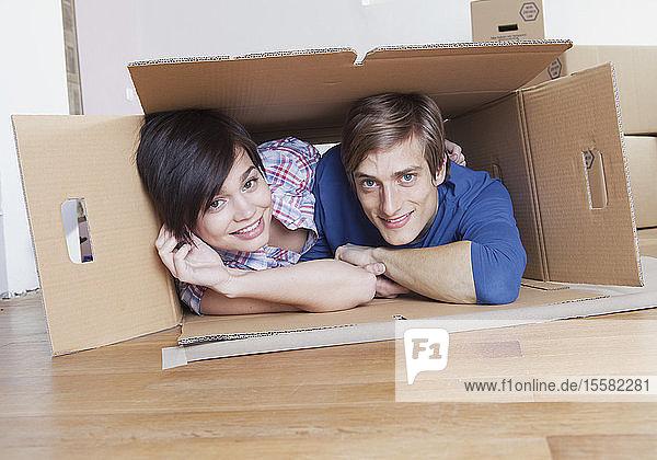 Junges Paar in Pappkarton  lächelnd  Porträt