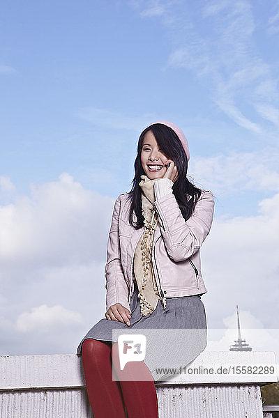 Deutschland  Köln  Junge Frau am Telefon  lächelnd