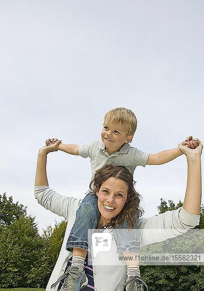 Mutter trägt Sohn auf den Schultern und lächelt