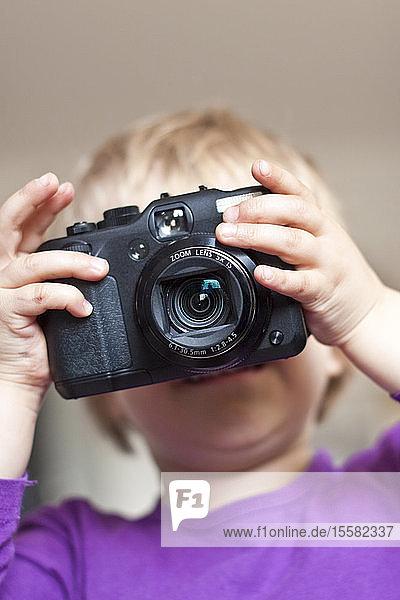 Little girl's face behind digital camera