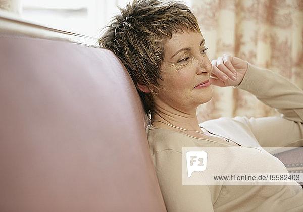 Reife Frau sitzt auf dem Sofa und lächelt