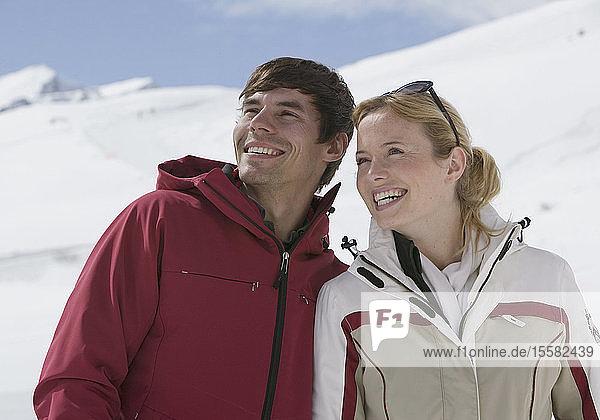 Österreich  Tirol  Junges Paar schaut weg  lächelt