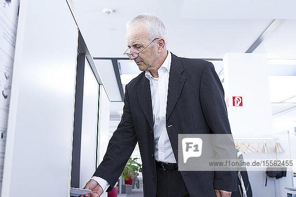 Geschäftsmann am Aktenschrank im Amt