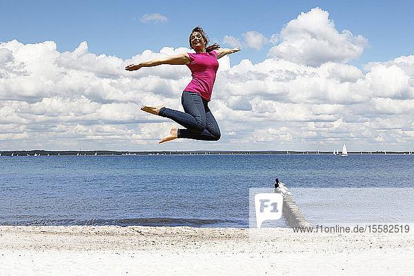Glückliche junge Frau springt am Strand in die Luft