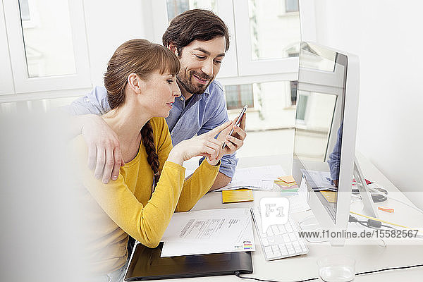 Couple with cell phone at desk in home office