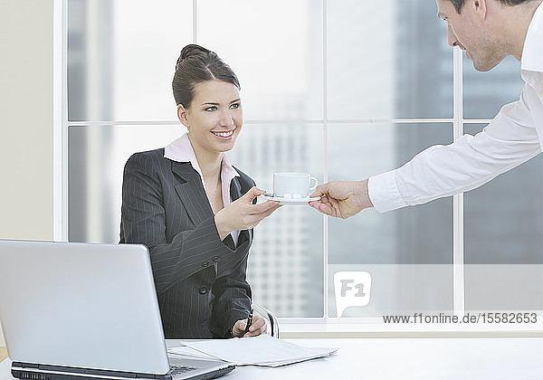 Kollege bringt Kaffee für Geschäftsfrau,  die im Büro arbeitet