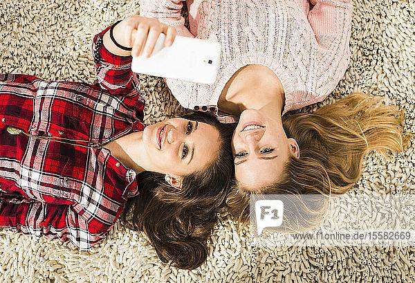 Zwei Freundinnen beim Selfie mit Smartphone zu Hause