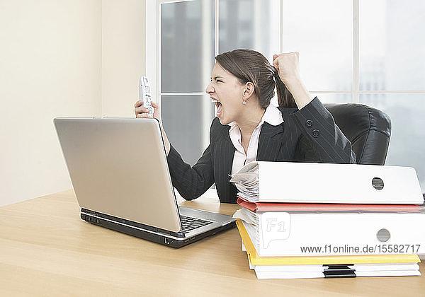 Geschäftsfrau schreit wütend auf Handy im Büro