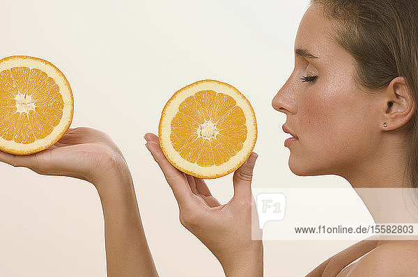 Junge Frau hält Orangenscheibe mit geschlossenen Augen