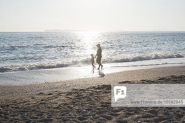 Griechenland  Parga  Mutter und Tochter gehen bei Sonnenuntergang am Strand spazieren