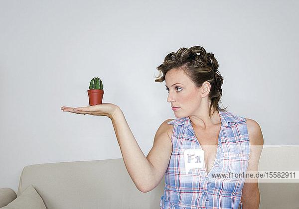 Junge Frau schaut auf winzigen Kaktus