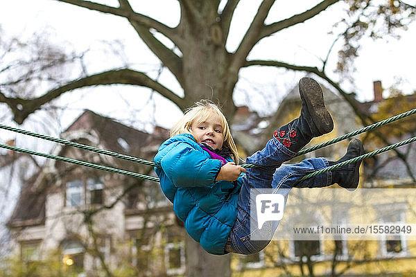 Little girl climbing on playground equipment