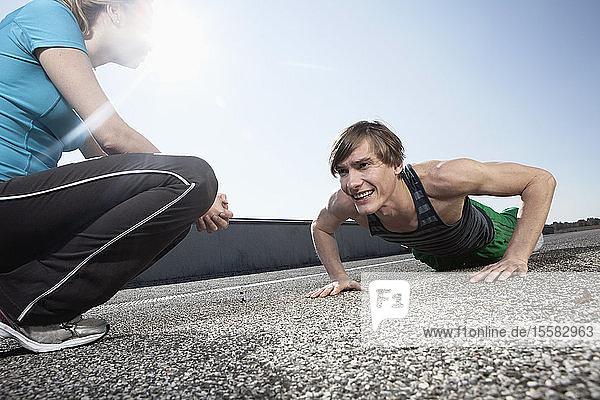 Germany  Bavaria  Munich  Young woman looking at man doing pushups