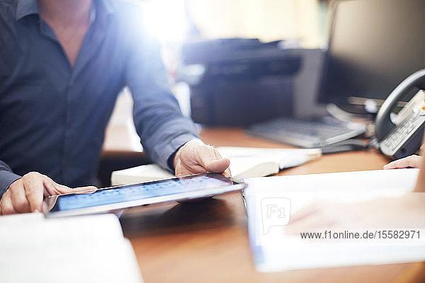 Mann am Schreibtisch mit digitalem Tablett in einer Bibliothek