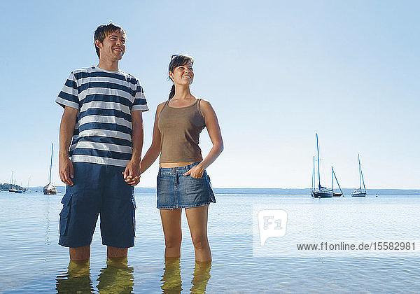 Deutschland  Ammersee  Junges Paar im See stehend  lächelnd