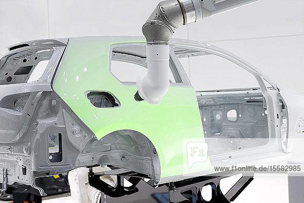 Roboter  der ein Auto lackiert