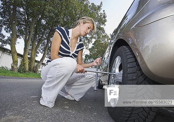 Deutschland  Augsburg  Junge Frau bei der Reparatur einer Reifenpanne