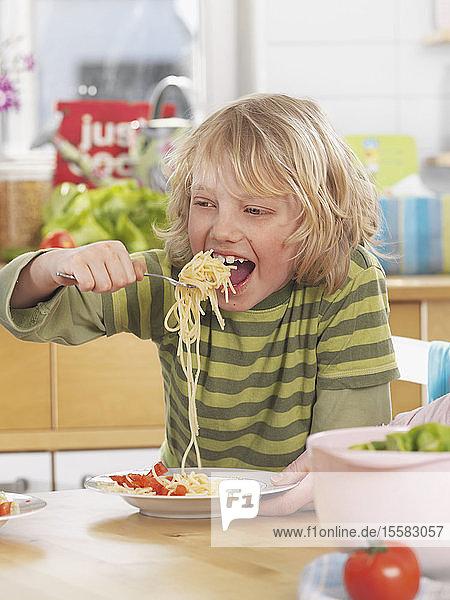 Deutschland  Augsburg  Junge isst zu Hause Spaghetti