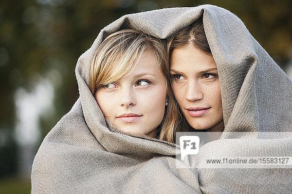 Deutschland  Köln  Junge Frau mit Decke  lächelnd