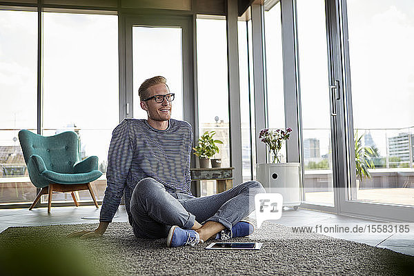 Smiling young man sitting on carpet with tablet at home