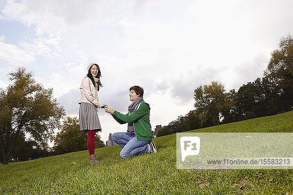 Deutschland  Köln  Junger Mann schlägt Frau im Park vor  lächelnd