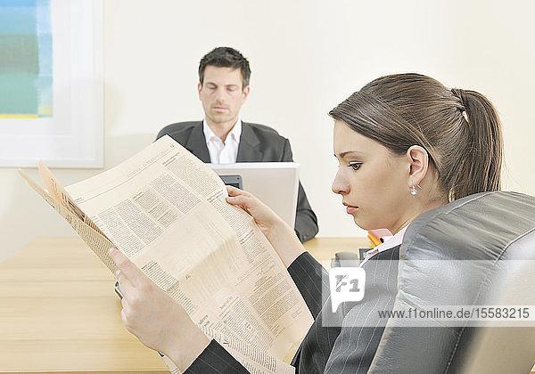 Geschäftsmann arbeitet am Laptop und Frau liest Zeitung im Büro