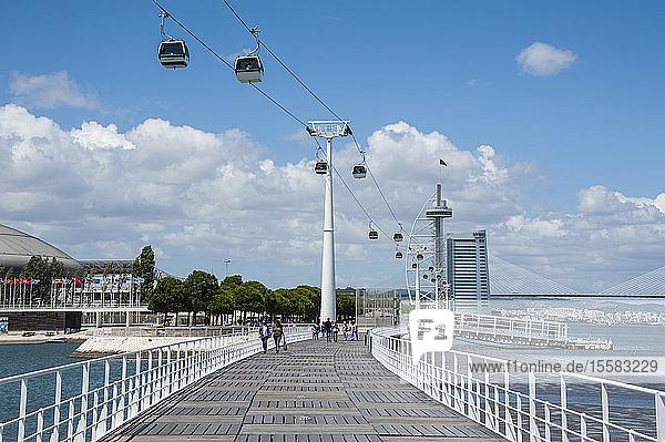 People walking on bridge leading towards Vasco da Gama Tower over river in city against sky  Lisbon  Portugal
