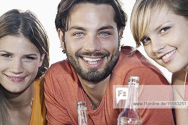 Deutschland  Köln  Junger Mann und Frau mit Bierflaschen  lächelnd  Porträt