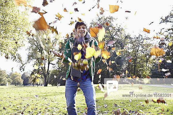 Deutschland  Köln  Junger Mann spielt mit Blättern im Park  lächelnd  Porträt